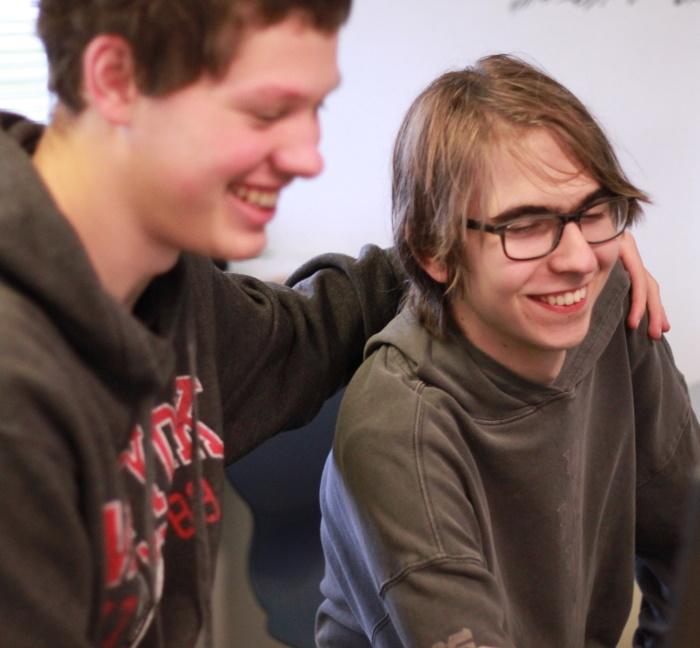 Billedet viser to personer, der krammer, med blikket rettet mod en skærm